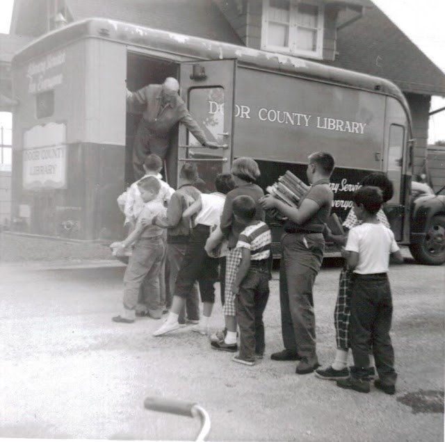 Children in Door Country line up to visit the bookmobile