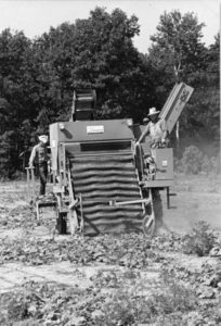 a black and white image of a mechanical pickle harvester and two men operating it