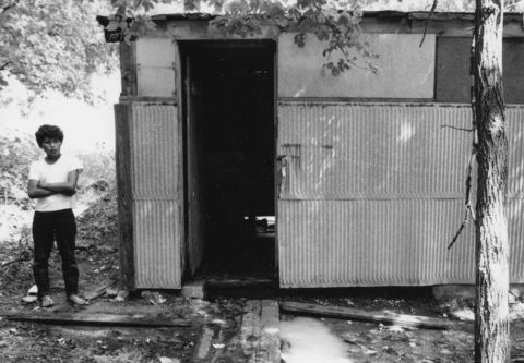 a boy standing beside the shower facilities at a migrant workers village. the facility has no visible door, metal sides and no lighting.