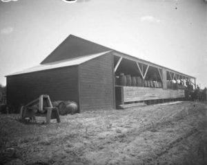 a black and white picture of an open-sided barn with pickle barrels stacked inside