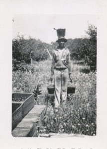A migrant worker with three pails of cherries at the Fardig Orchard in Ephraim, WI, c. 1930. Photograph courtesy of the Ephraim Historical Foundation.