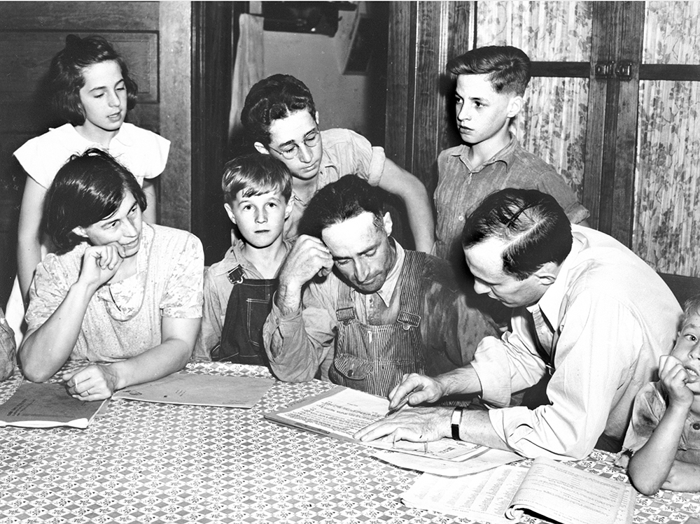 Farm Security Administration (FSA) county supervisor reviewing a farm plan with a Wisconsin farmer and his family. Photograph by John Vachon, September 1939, courtesy of the Wisconsin Historical Society, Image ID 25048.