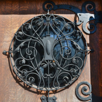 Wilson Place Door, a wooden door showing a wrought iron metal grill over a window.