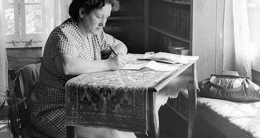 A woman sits writing at a desk