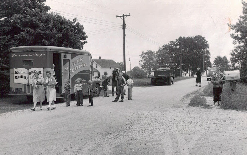 Children wait in line to borrow books from the Door County bookmobile. Image courtesy of the Egg Harbor Historical Society.