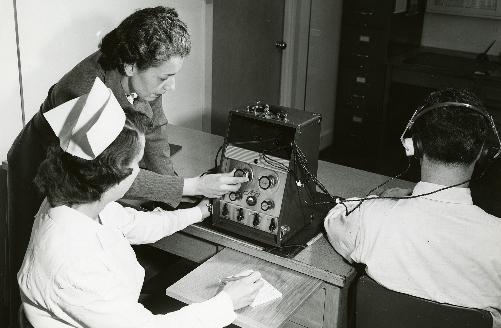 An Employers Mutual Occupational Health Consultant administering a hearing test c. 1960. Photograph courtesy of the Marathon County Historical Society.
