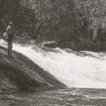 a black and white image of a man fishing in the wolf river
