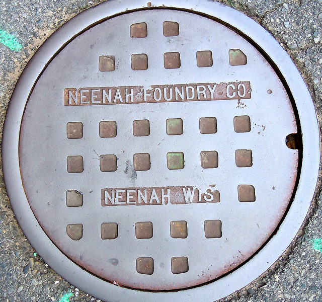 an image of a round metal manhole cover
