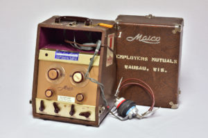 Color photograph of a audiometer, which looks a bit like a box with knobs and wires coming out of it.