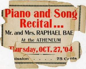Image of a slightly torn poster in red and black advertising a concert by Raphael Baez