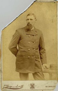 A sepia-toned portrait of a man standing with his arm behind his back.