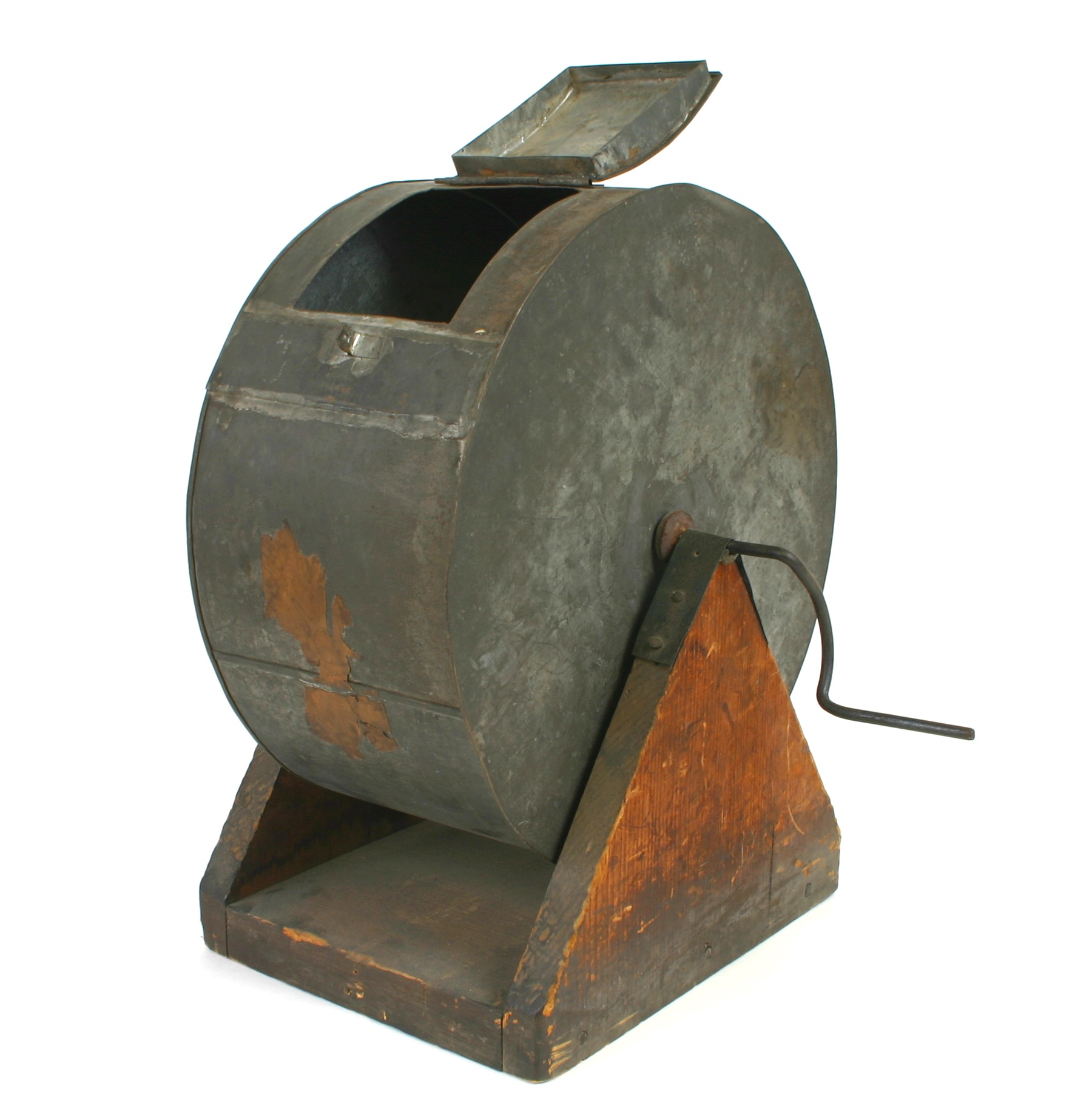 A metal cylinder with a handle for turning and a hatch for selecting items from within, on a stand