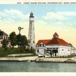 A color postcard showing a lighthouse and lifesaving station in wisconsin.