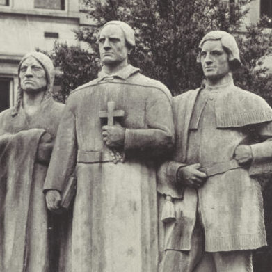 detail of Sculpture showing three figures, the central figure is a french priest with a Native American man to his right and a french colonial man to his left