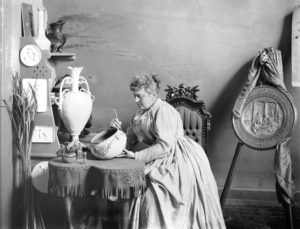 A portrait of a woman painting a ceramic bowl at a table.