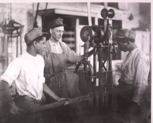An image of a teacher and two teenaged boys working in a metalsmithing shop at the Illinois State Reformatory in 1938.