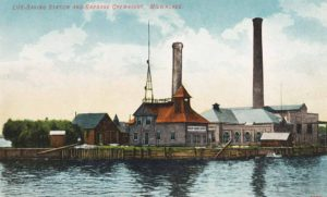 color postcard of an early lifesaving station showing an antennae, towers and houses