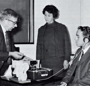 A black and white image of three people testing an audiometer, one man has headphones on his ears while a woman looks on and another man is testing a read-out from the machine.