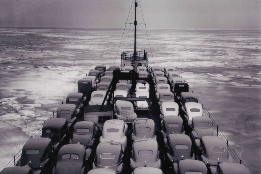 A black and white image showing lines of model A cars lines up on the deck of a whaleback ship