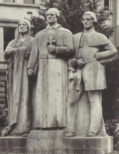 Sculpture showing three figures, the central figure is a french priest with a Native American man to his right and a french colonial man to his left