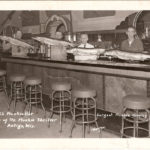 An old postcard showing four men behind a bar holding very large muskies for display