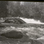 a black and white photo of a man fly fishing in the Wolf River standing in the rapids