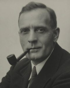A black and white portrait of Edwin Powell Hubble smoking a pipe