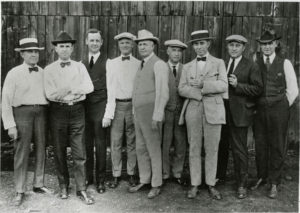 An image of nine men in suits posing in front of a barn door.