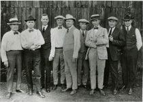 An image of seven men in suits posing in front of a barn door.