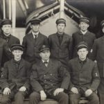Group portraits of nine men in uniform before a boat.