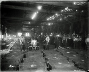 A black and white image of the shop floor of a factory showing workers posing with machines