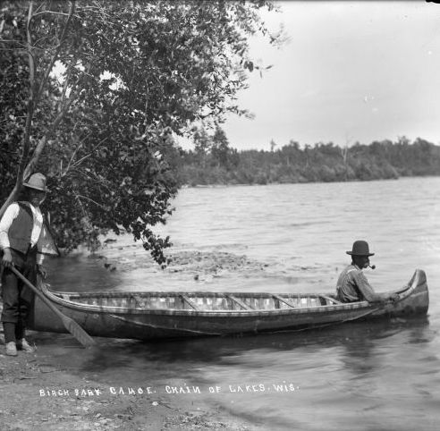 Two men and a birch bark canoe beside a lake