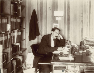 a sepia portrait of a man with a large mustache leaning on his hand at a desk while writing one some papers