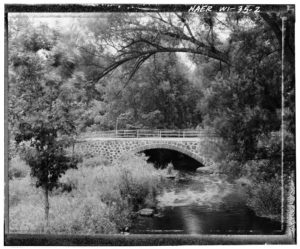 black and white photo of the wolf river going under a bridge in a wooded area with a meadow on the left side