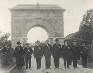 Black and white image showing a group of men in suits standing in front of the Camp Randal arch with Old Abe on top of the monument