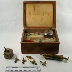 Image of a wooden box with several glass bells of different sizes within. A brass hose with different nozzle sizes sits beside it.