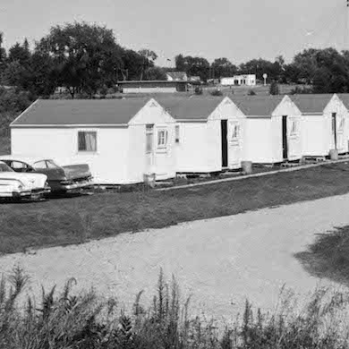 a black and white photo showing a row of identical tiny white-painted cabins