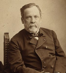 A portrait of Louis Pasteur with hands folded looking at the viewer