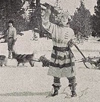 A still from a 1920s movie featuring a lead wearing a point blanket coat. shown here waving at the viewer in the snow