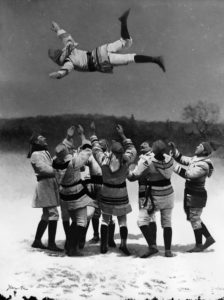 Image from an early film showing a group of people wearing point blanket coats tossing another person in the air as part of a game.