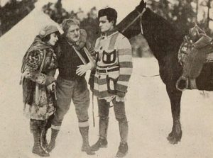 a film still from the 1919 movie, A wilderness trail, showing three people standing before a horse in the woods. One man is wearing a short point blanket coat.