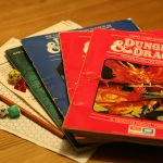 a color photo of several early Dungeons and Dragons rulebooks with dice