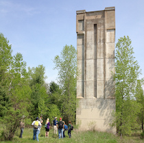 A picture of the Kickapoo Valley Reserve dam tower showing a concrete tower rising nearly 100 feet above a grassy lawn