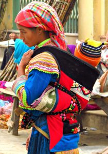 A woman wearing a baby sash and carrier in a market