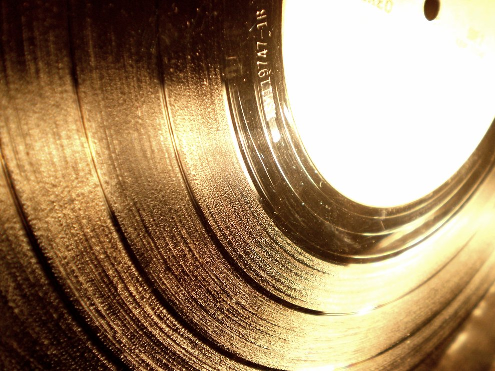 A close-up of a black vinyl record showing the grooves which create the sound