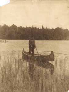 A Menominee man standing in a canoe on the shores of a lake in 1922.