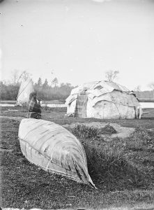 A black and white image of a Ho Chunk person leaning on a beached canoe with a wigwam and tipi in the background