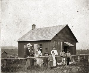 a black and white photo of the Pleasant Ridge schoolhouse showing several school children and two adults in front of the one room building