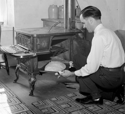 A black and white photo of a man putting a pasty in a wood stove