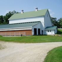 A color photo of a large white barn built into an embankment